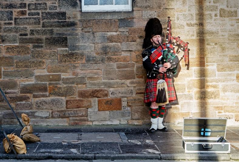 Un gaitero voluntario en la explanada del castillo. Parte de lo que reciben lo donan a caridad.